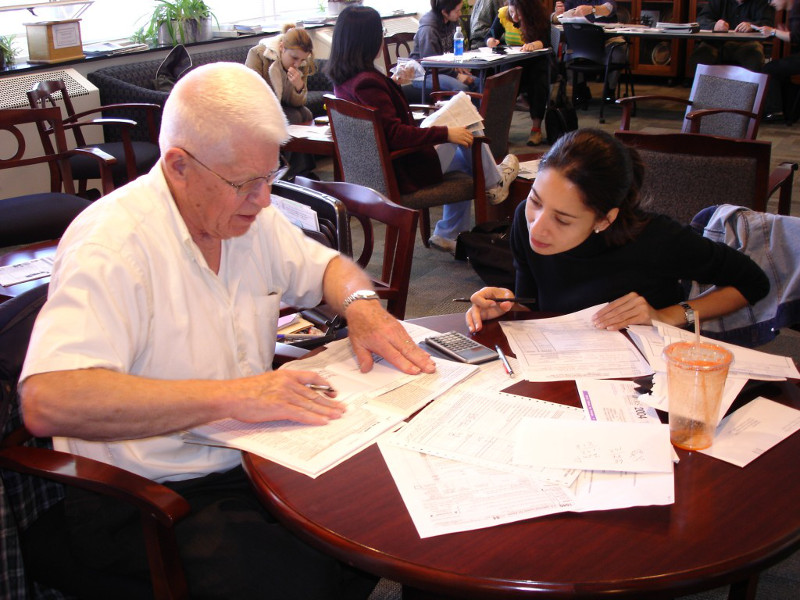 Tax-Volunteer-Bob-Malcom-helps-a-Greek-citizen-file-her-2004-US-Tax-Return-in-last-years-program
